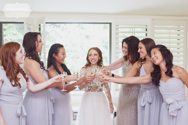 The bride is surrounded by her bridesmaids for a toast before the wedding at the Topnotch Resort in Stowe, VT.