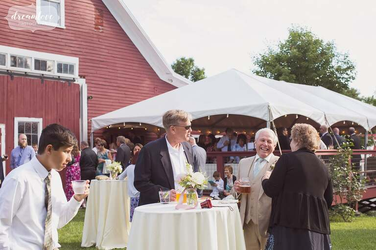 Guests enjoy drinks outside of the Bishop Farm barn during cocktail hour.