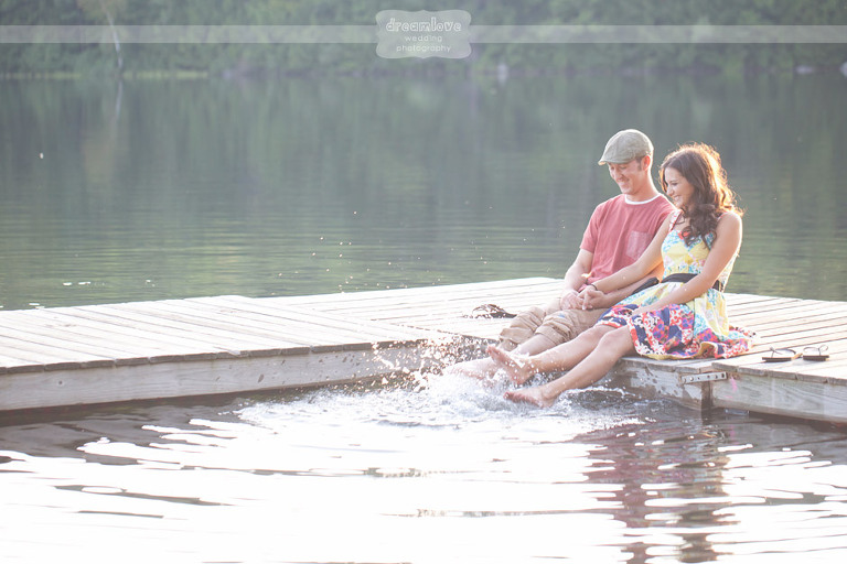 Couple sitting on a dock and splashing their bare feet in water during an engagement session in NH.