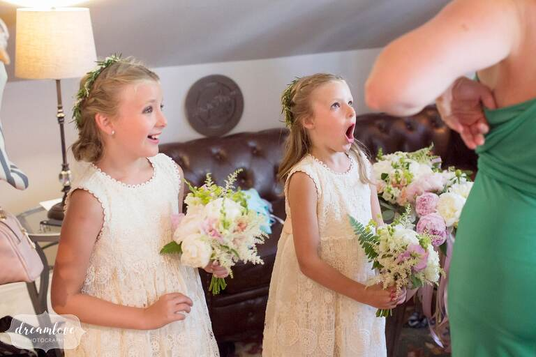 Documentary wedding photos of the flower girls seeing bride for first time.