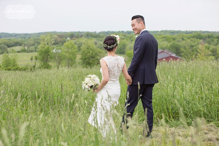 Bride and groom walking through field by Hudson Valley wedding photographer.