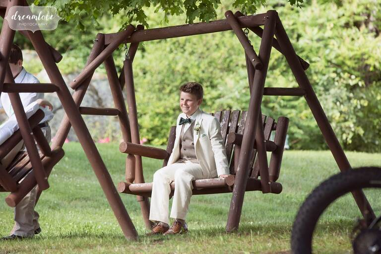 The ring bearer swings on bench at Bishop Farm.