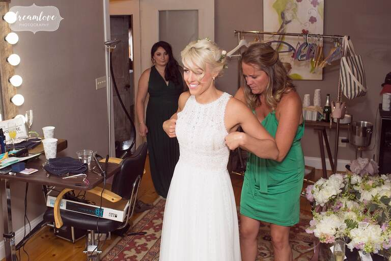 The bride puts the dress on with bridesmaids at Bishop Farm.
