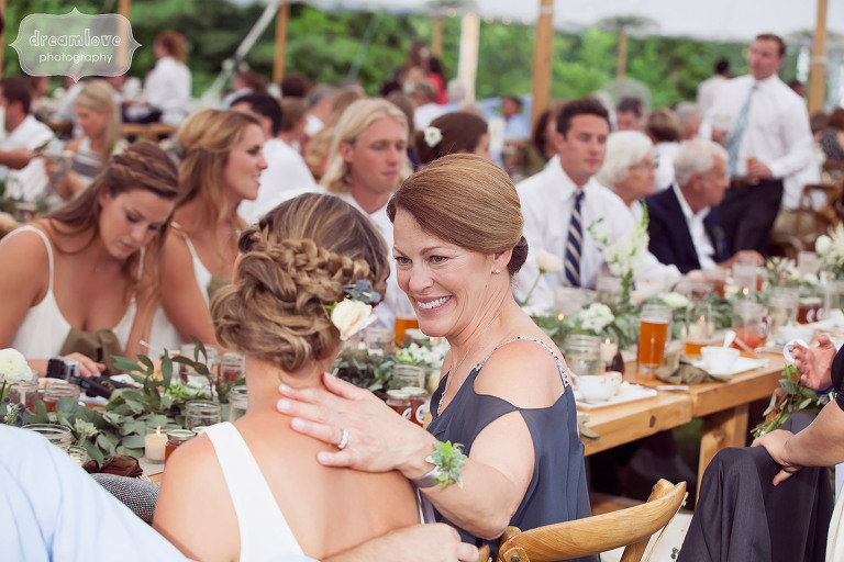 Sweet candid photo of the mother of the bride with her daughter during speeches at the wedding reception at the 1824 House in VT.