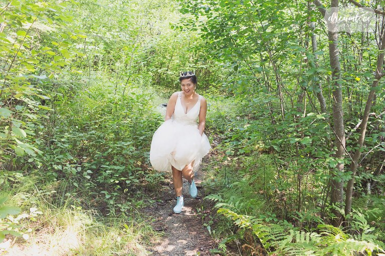 The bride wears baby blue hunter boots while walking through the forest in NH.