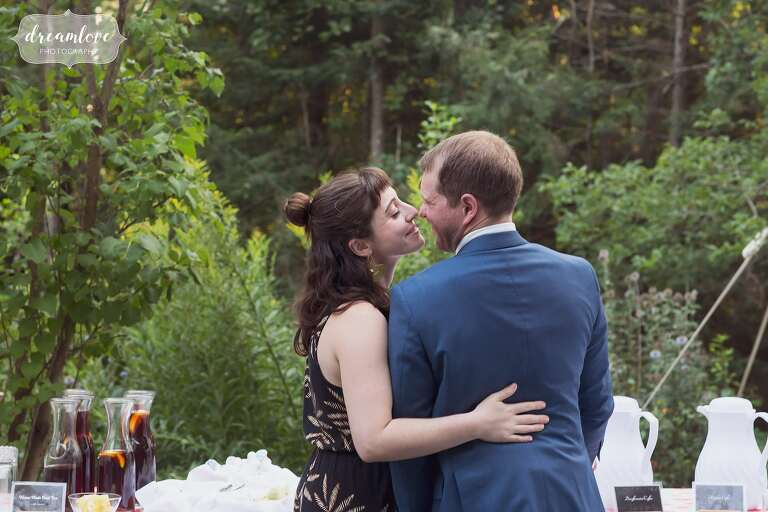 Candid photo of wedding guests kissing.