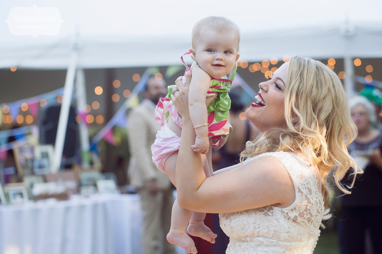 Bride holds a baby up in the air after Cape Cod wedding in MA.