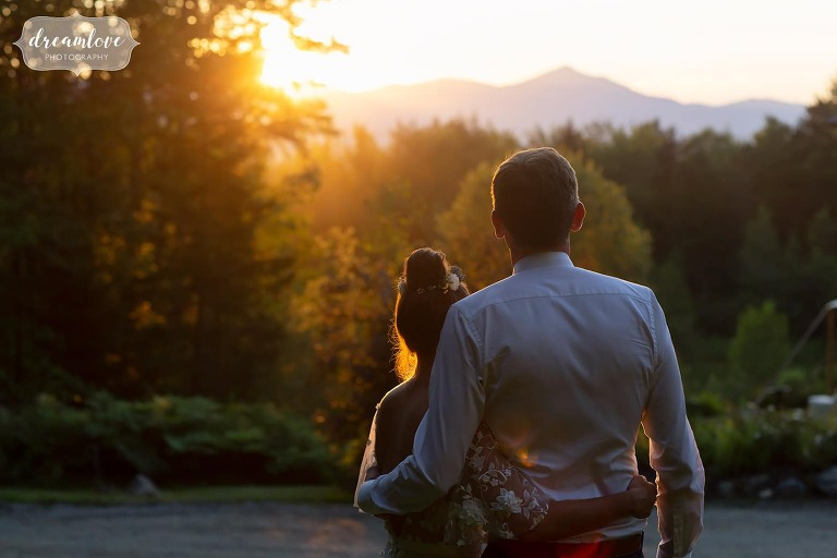 Couple looks at the mountains during sunset in Stowe, VT.