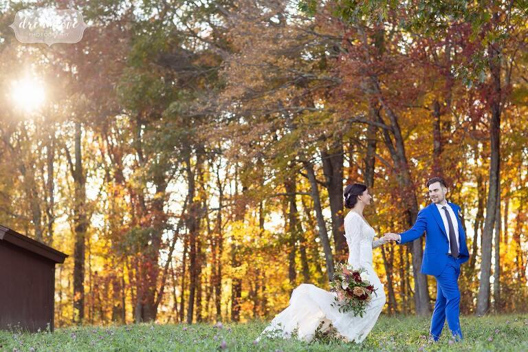 Groom holds bride hands through woods at October wedding at Zukas Barn.