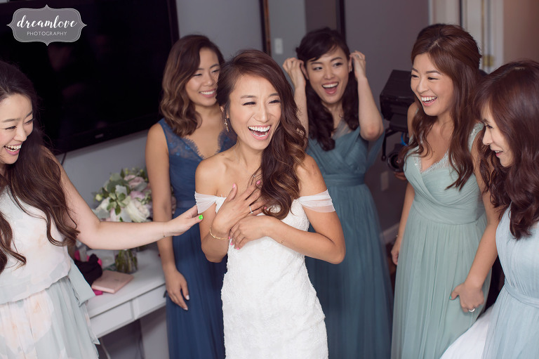 Happy wedding photography of the bride getting her dress on with help of bridesmaids at the Inn on Main in Wolfeboro.