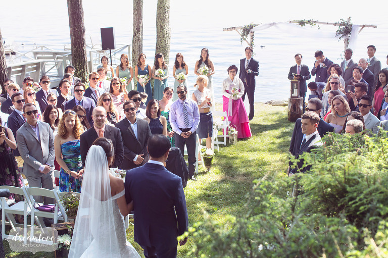 The bride and her father walk down the aisle at this lakeside ceremony in Wolfeboro, NH.