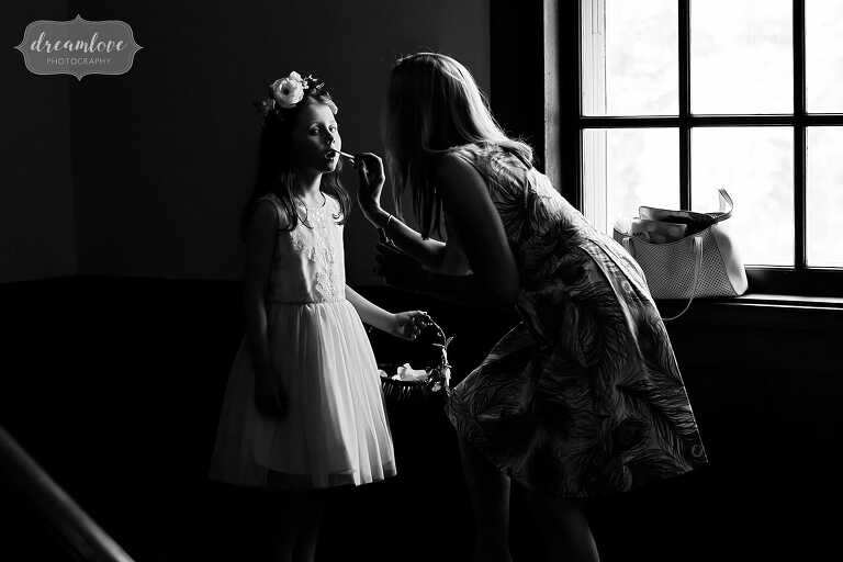 Documentary wedding photography of flower girl putting on lipstick at south shore wedding.