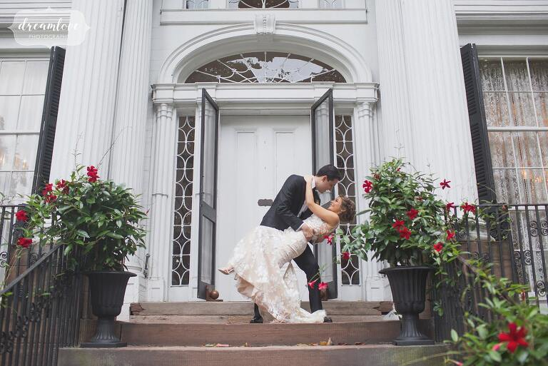 The bride and groom have a Hollywood kiss in front of the Linden Place mansion.