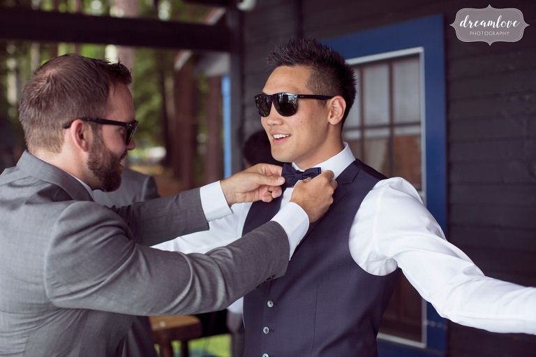 A groomsman helps out this charismatic groom by tying his bowtie before his backyard wedding on Lake Wentworth in Wolfeboro, NH.