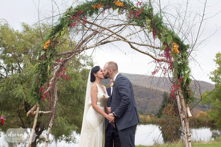 The bride and groom kiss under a woodsy wedding arbor for this Catskills backyard wedding in Roxbury, NY.