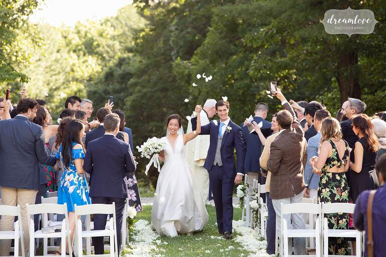Bride and groom exit ceremony while guests throw flower petals.