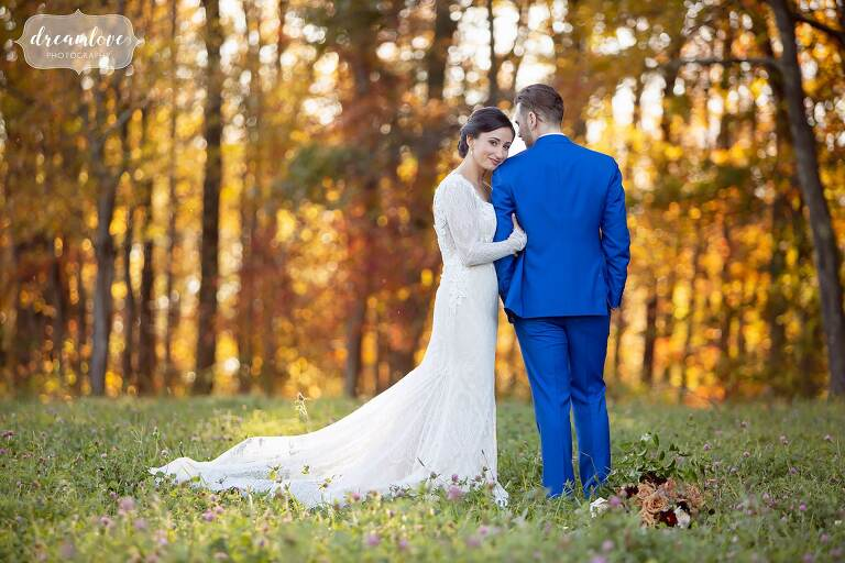 Bride wraps her arms around groom with bright fall foliage at Zukas Barn.