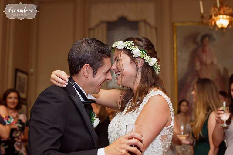 Joyful wedding photography of the bride and groom laughing while dancing in the ballroom at the Crane Estate venue in MA.