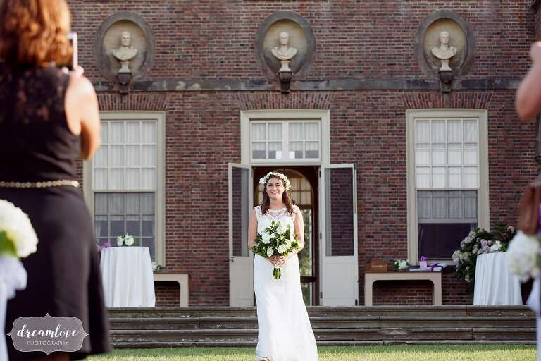 Bride walks out of the Crane Estate Castle Hill house down the aisle of her outdoor wedding ceremony.