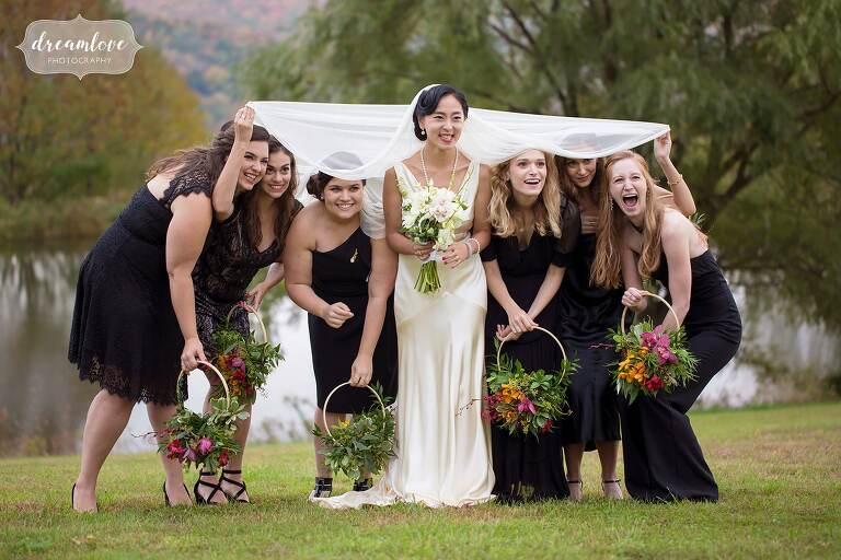 Funny photo of the bridesmaids hiding under bride's veil in Roxbury, NY.