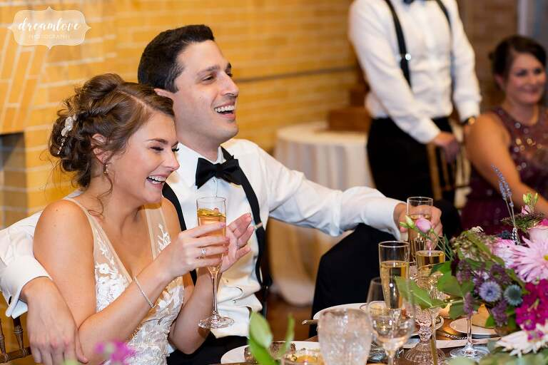 The bride and groom laugh during speeches at the Linden Place in RI.
