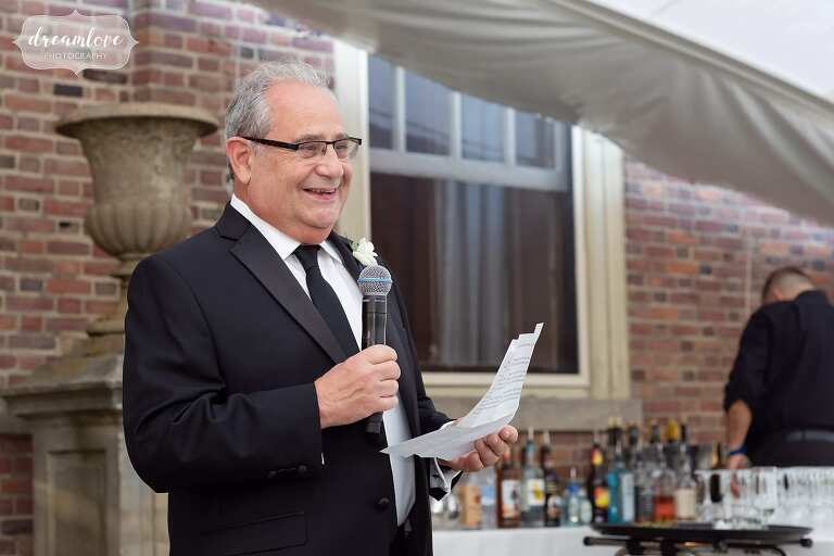 Dad gives toast on patio at Crane Estate Great House wedding.