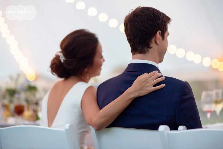 Romantic wedding photo of bride and groom listening to toasts.