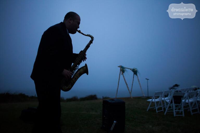 Artistic wedding photo at twilight of saxophone player.