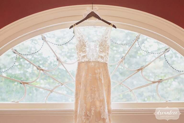 The bride's dress hangs in an antique window at this Bristol, RI estate wedding venue.