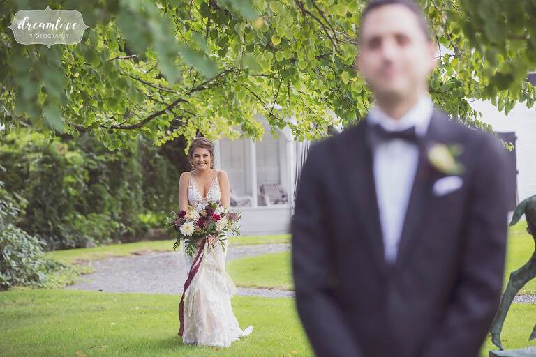 The bride and groom have their first look on the lawn at the Linden Place.