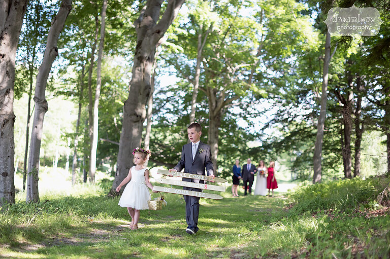The flower girl and ring bearer walk through the woods before this June wedding in Sugarbush, VT.