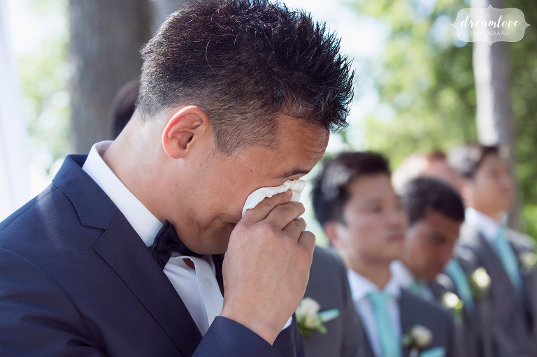 The groom begins to cry when he sees the bride walking down the aisle at this backyard wedding in Wolfeboro, NH on the lake.