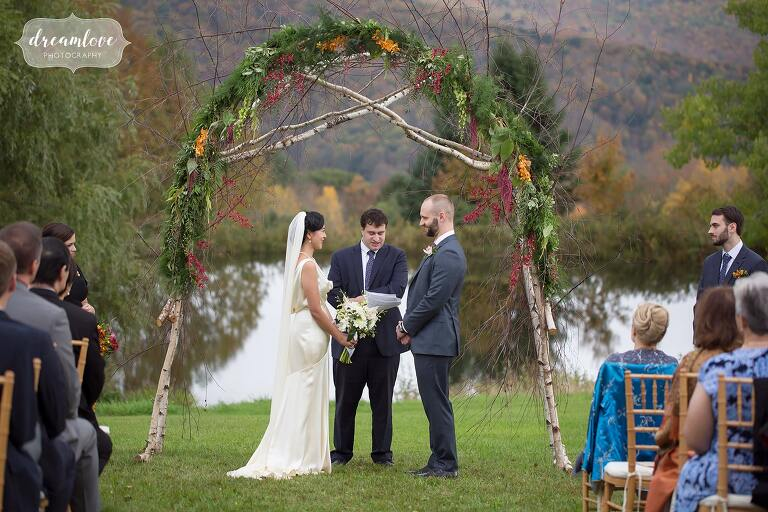 The bride and groom stand in front of their birchwood arbor with fall greenery in Roxbury, NY.