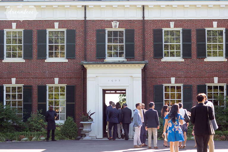 Guests mingle in front of brick wedding estate mansion on south shore.