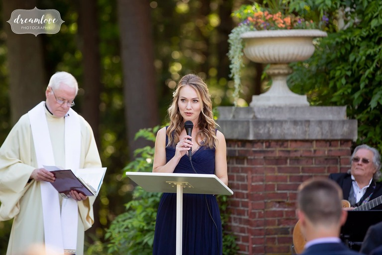 Bridesmaid speaks during garden wedding ceremony near Boston.