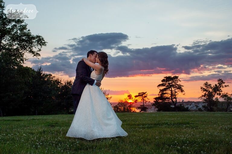 Bride and groom embrace with sunset behind them over the ocean at the Crane Estate.
