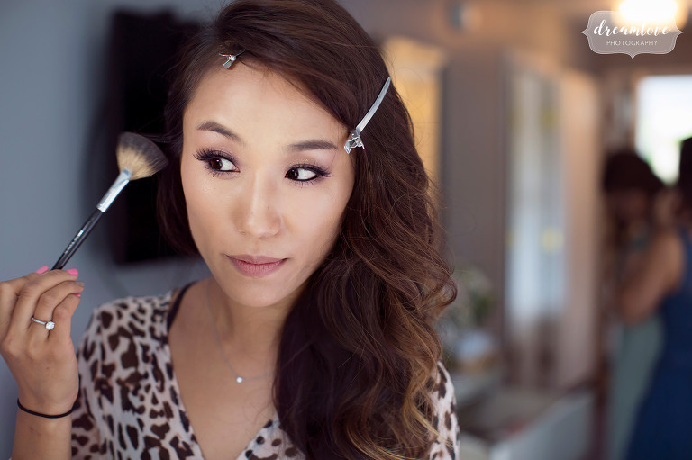 A Korean bride puts makeup on at the Inn on Main before her outdoor wedding in Wolfeboro, NH in July.