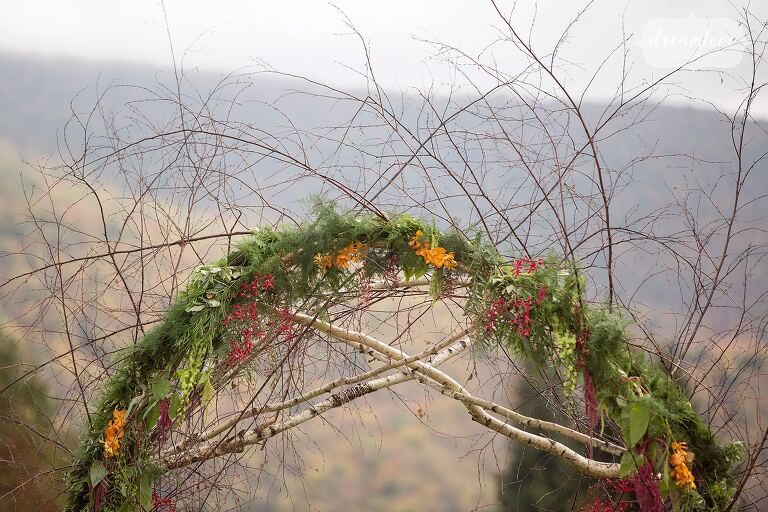 Beautiful rustic fall wedding ceremony arbor with bent birch wood and greenery in upstate NY.