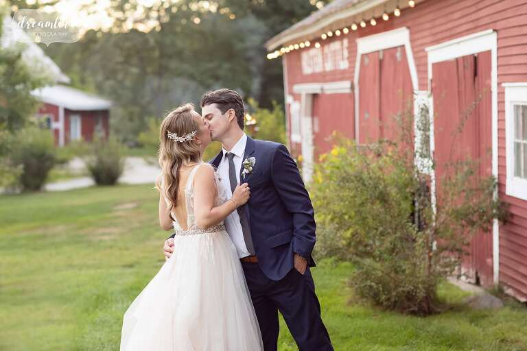 Bride and groom kiss in front of dairy barn.
