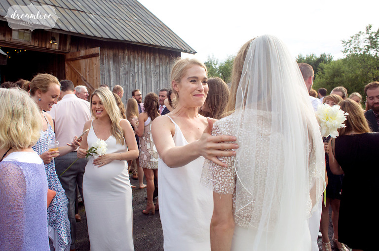 Candid photography of wedding guests mingling during the outdoor cocktail hour at the Comfort Farm barn in Stowe.