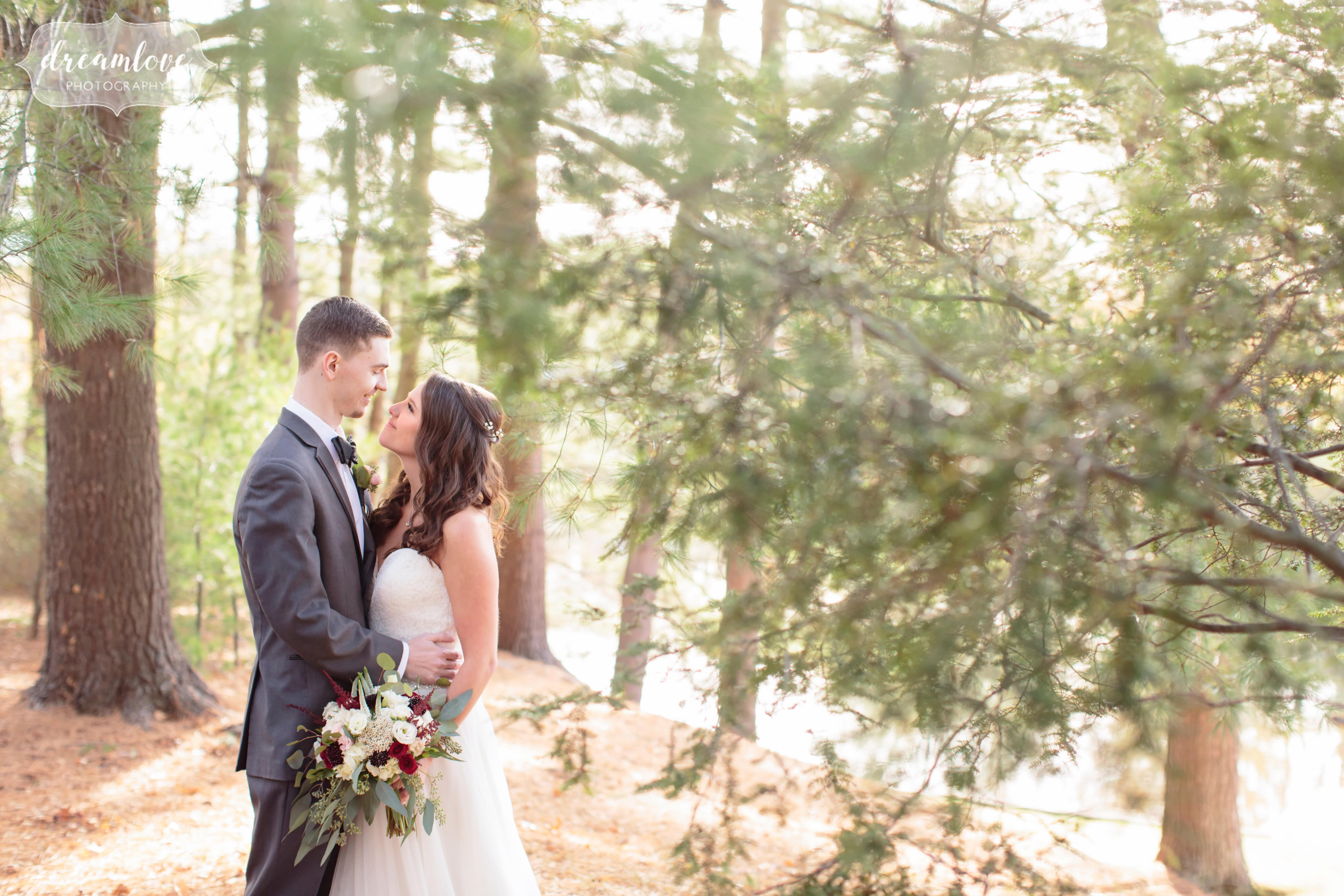 Bride and groom kiss in a sunbursty forest at the Pavilion on Crystal Lake.