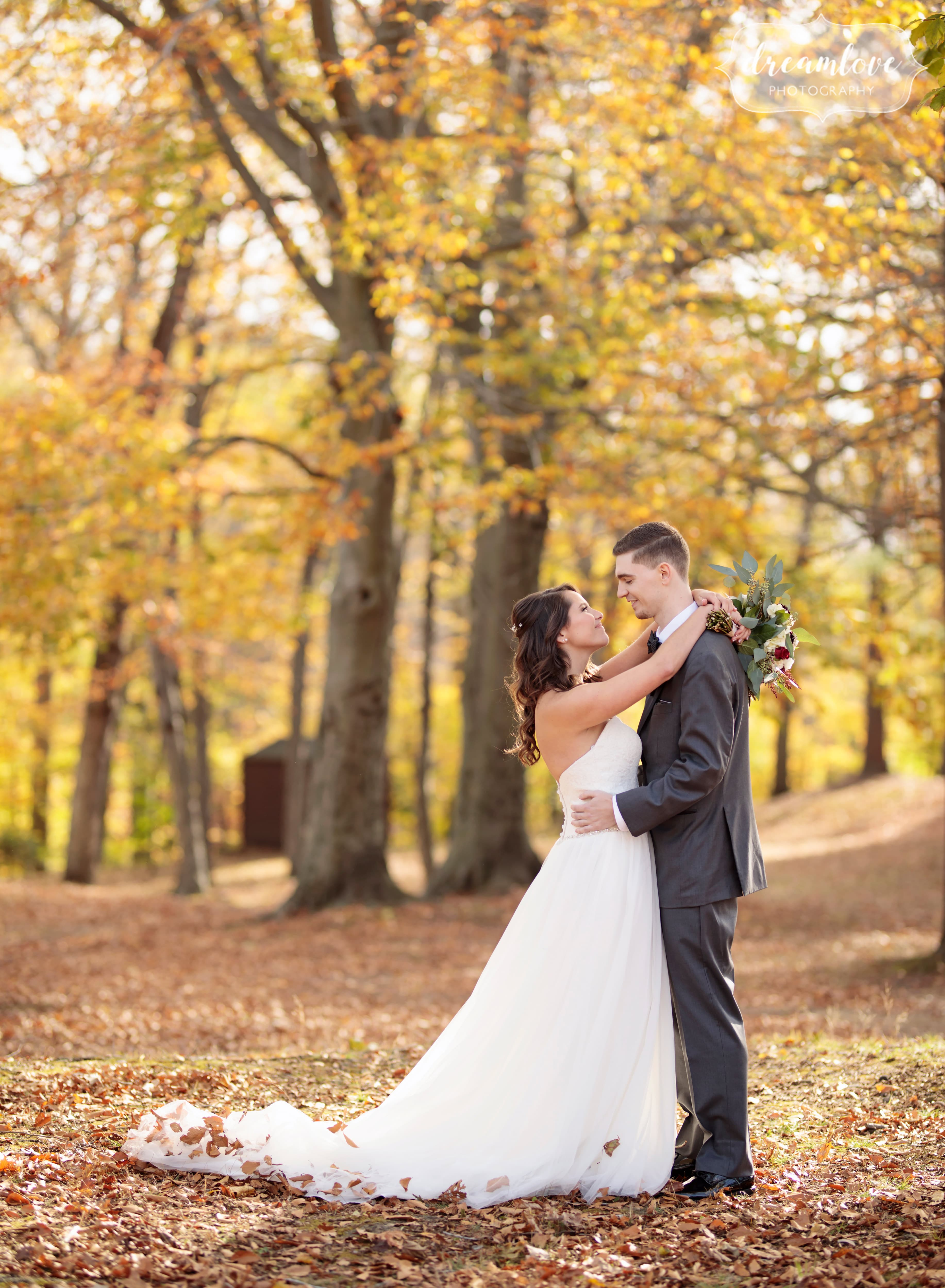 Bride and groom stand under yellow fall trees at their Pavilion on Crystal Lake wedding in November.