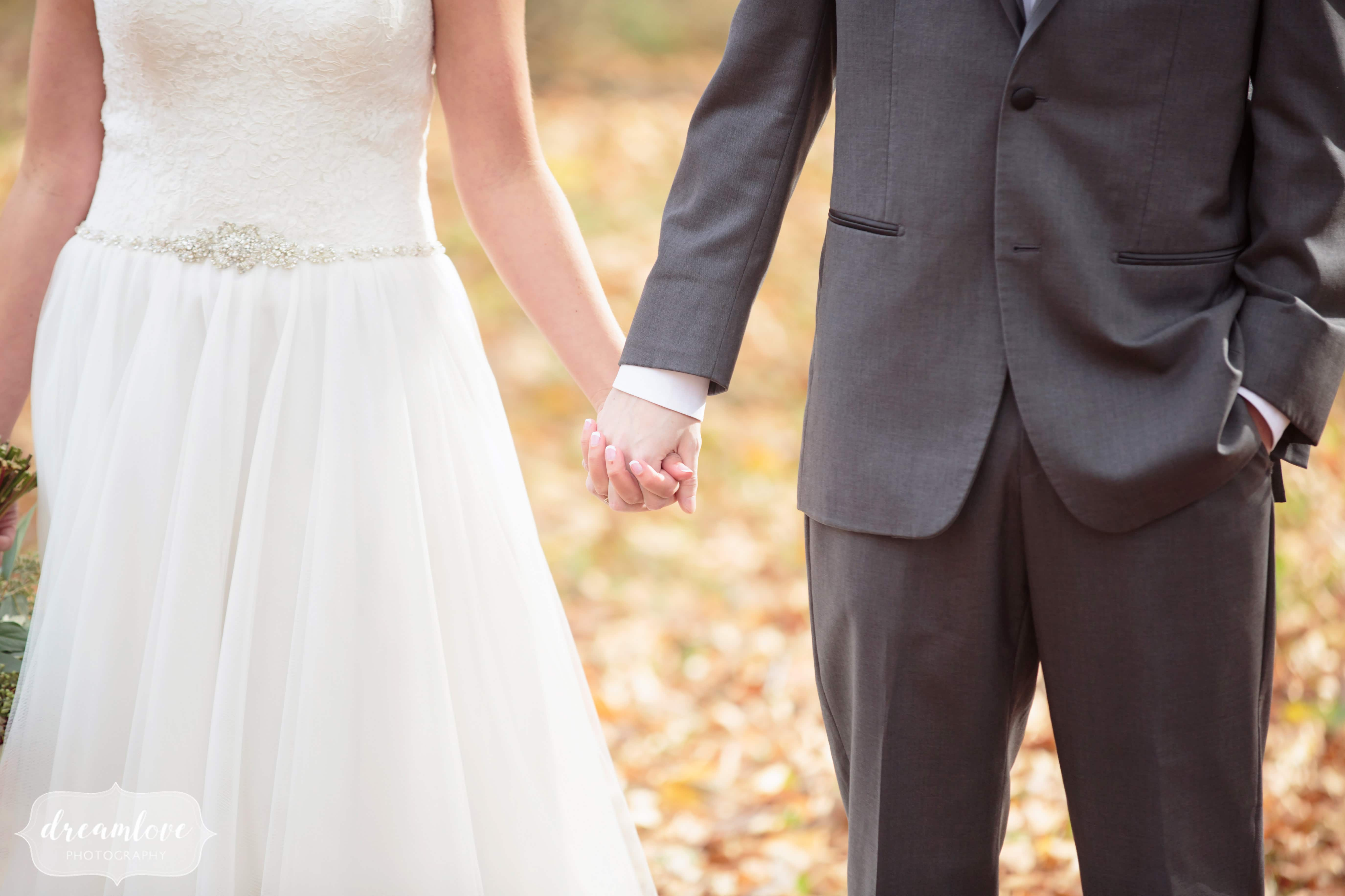 Unique wedding photography of the bride and groom holding hands in the forest.