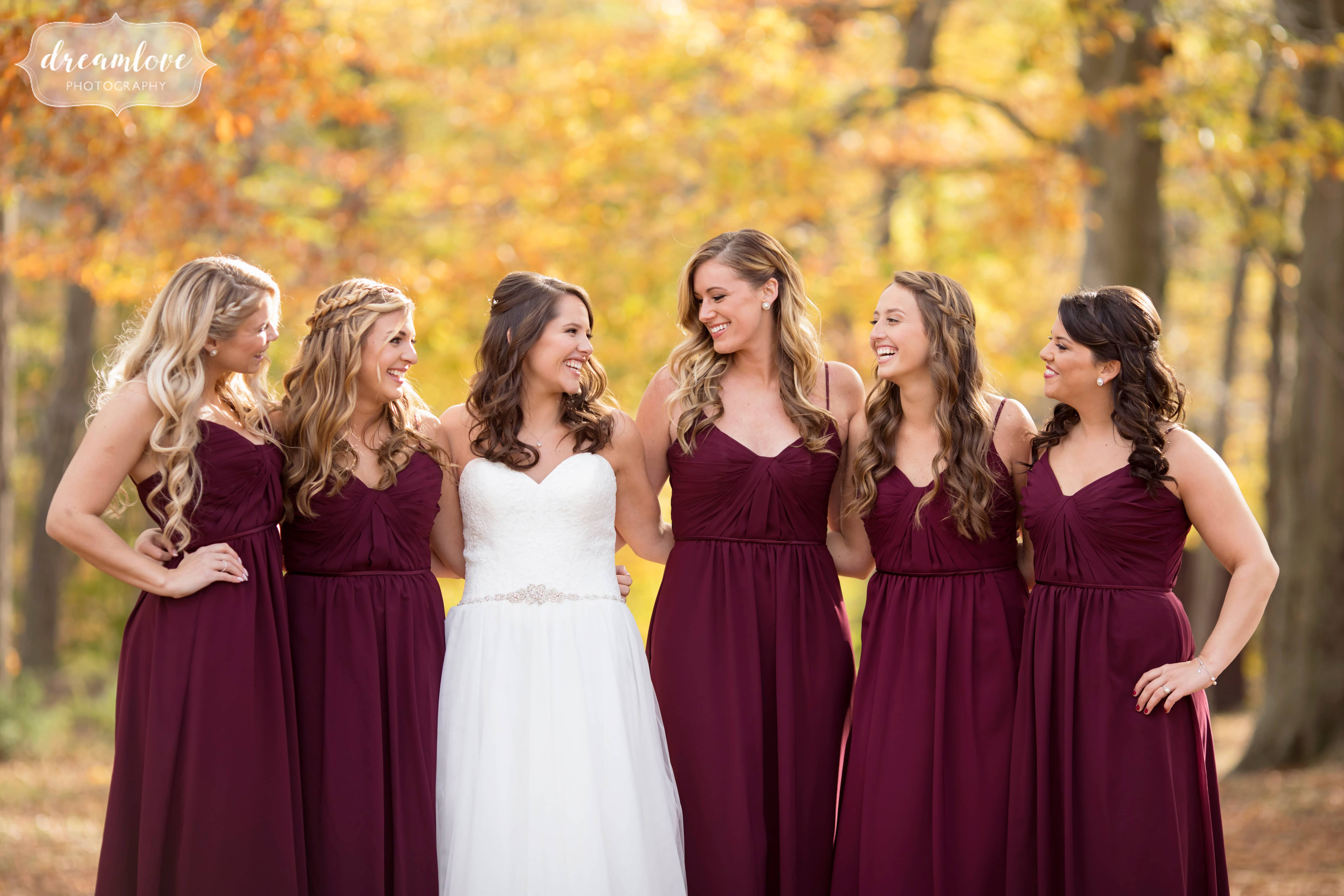 Soft light wedding photo of the bridesmaids in the woods with yellow trees in CT.