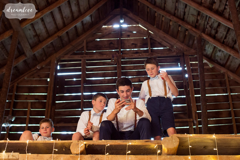 The ringbearers in their suspenders hang out in the loft of the Stowe Comfort Farm barn during a rainy wedding in Stowe.