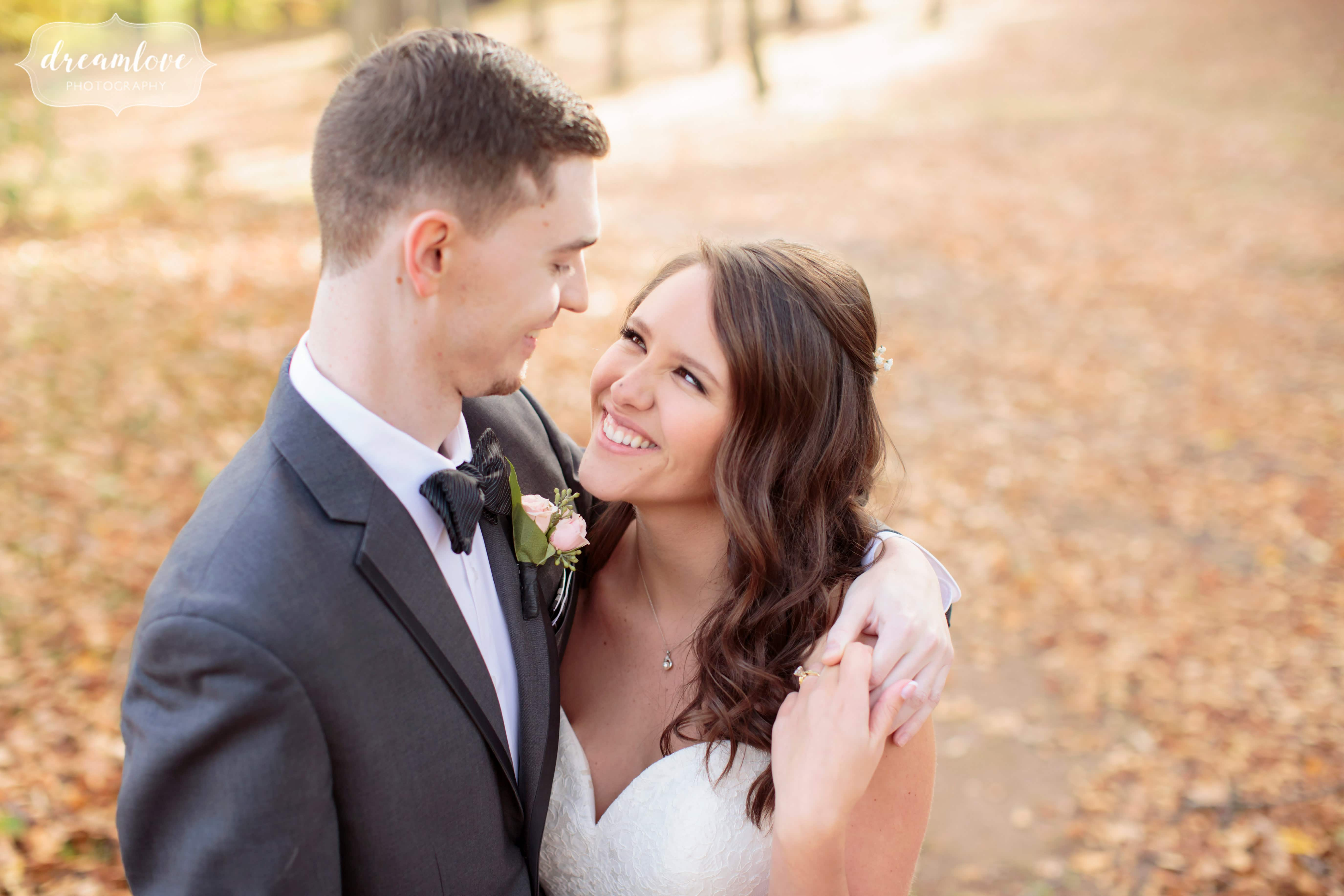 The bride and groom embrace in the woods before their forest wedding at the Pavilion on Crystal Lake in CT.
