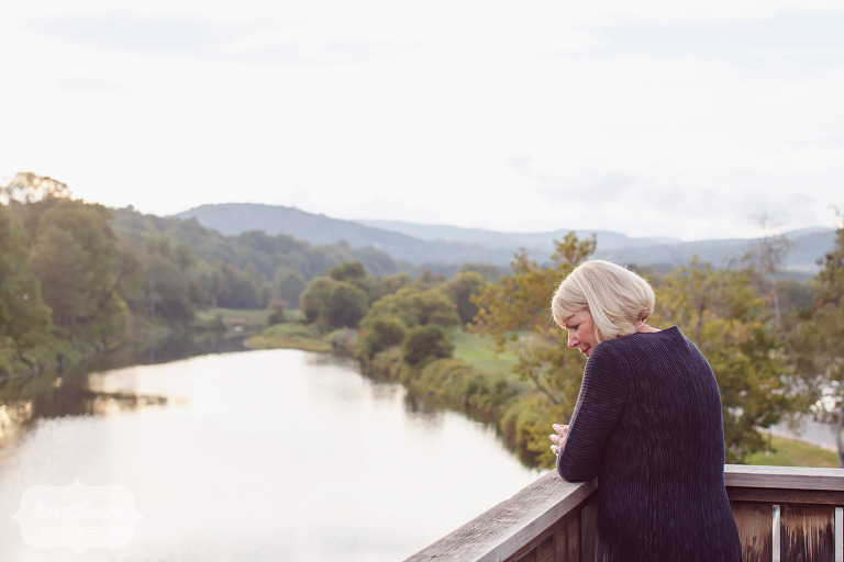 Candid photo of a wedding guest at the SImon Pearce Glass Factory in southern, VT looking out of the river.