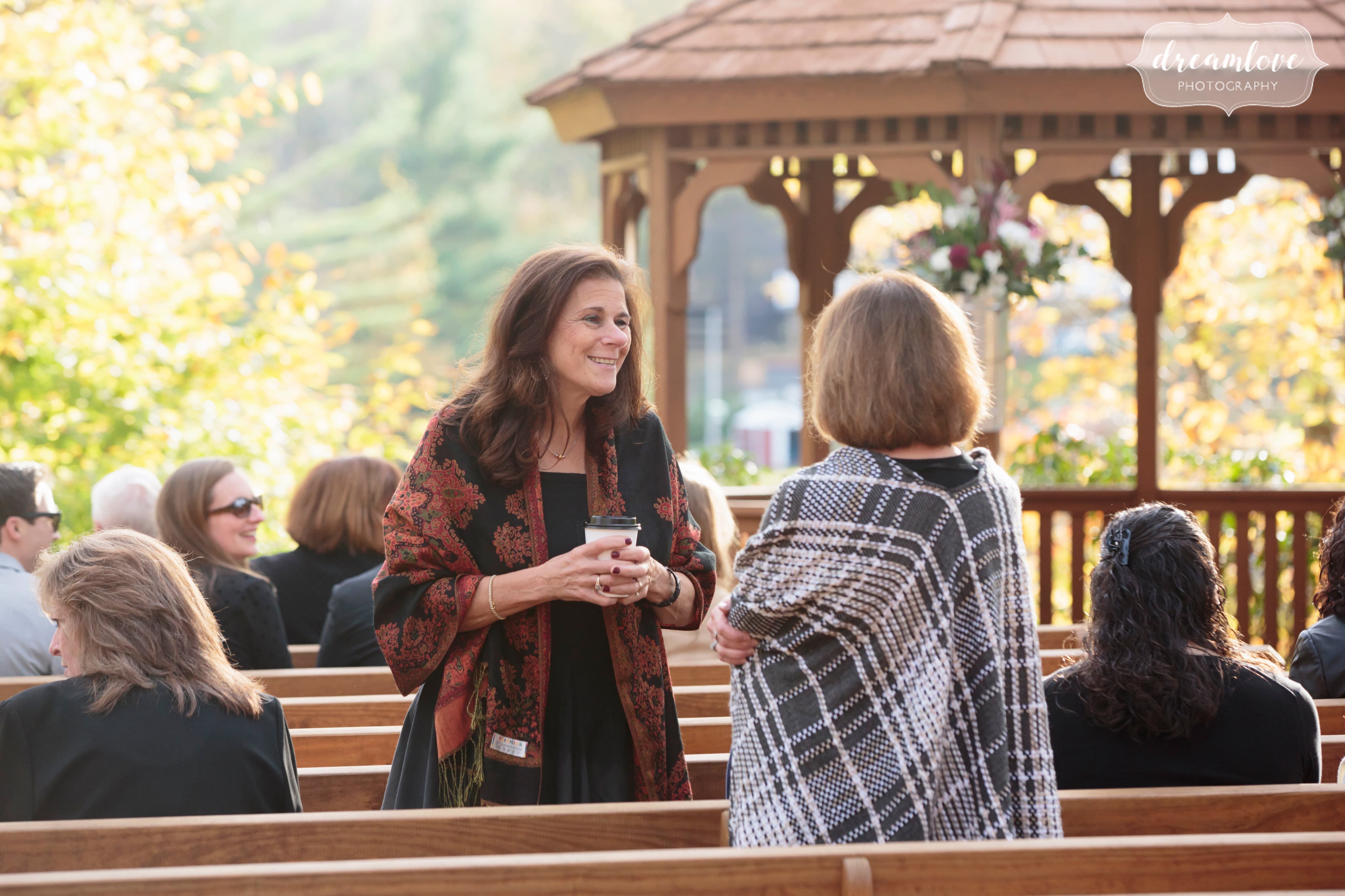 Wedding guests chat with each other before this outdoor woodsy wedding begins.