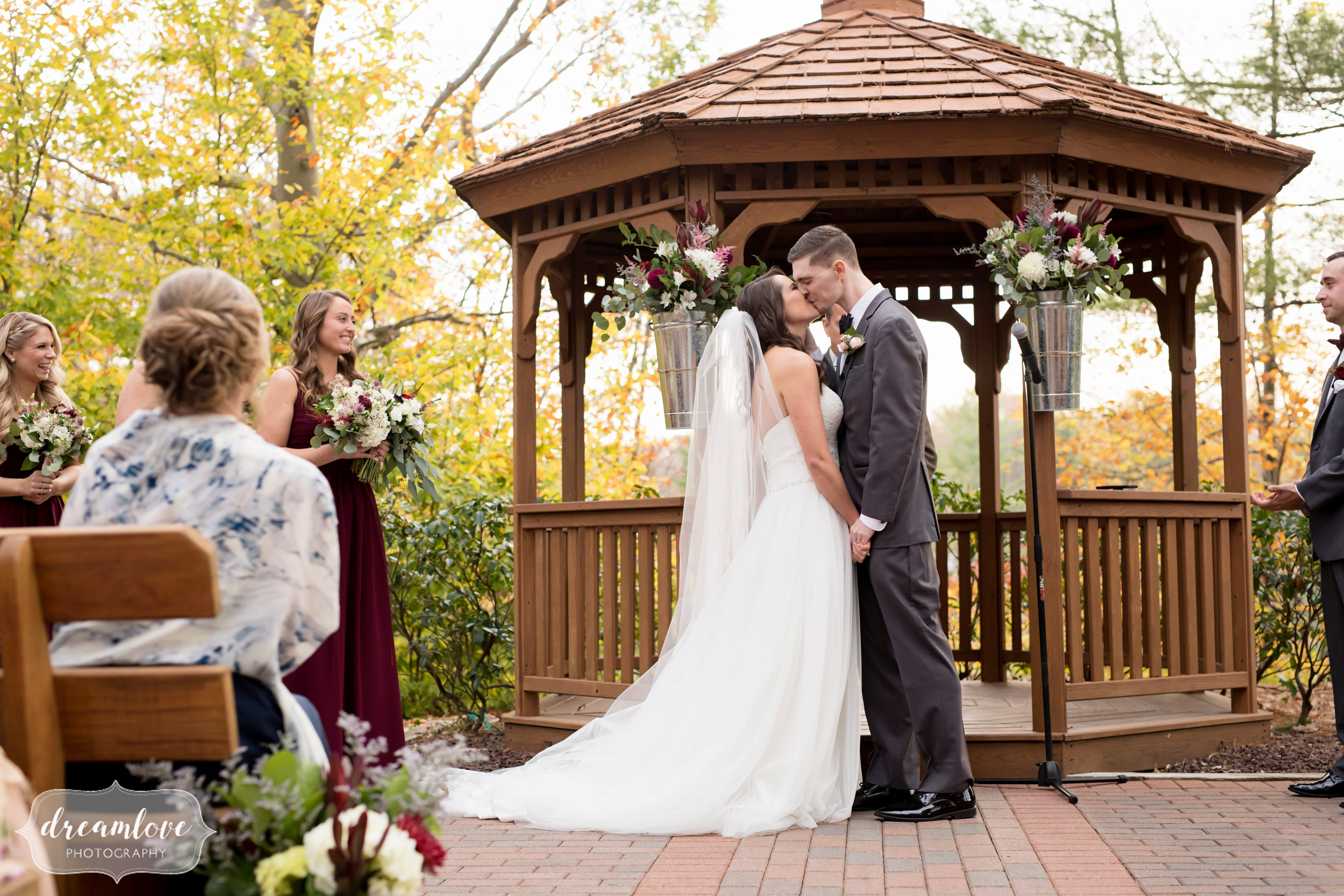 The bride and groom kiss at the end of their outdoor gazebo ceremony by the lake in Middletown, CT.