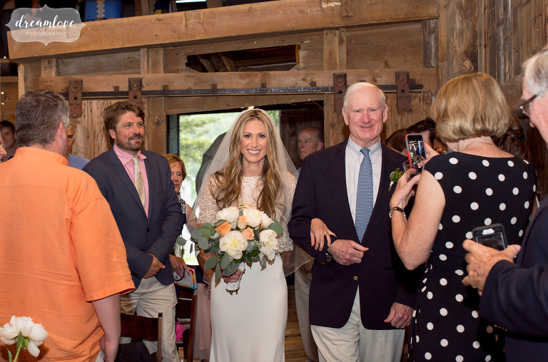 The bride and her father walk into the ceremony at the Comfort Farm in Stowe.